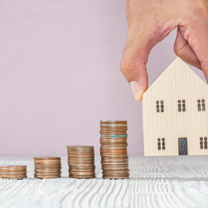 Hand choosing wooden house model and stack coin on white wood table, selective focus. Planning to buy property. Choose what's the best. Mortgage and real estate property investment.