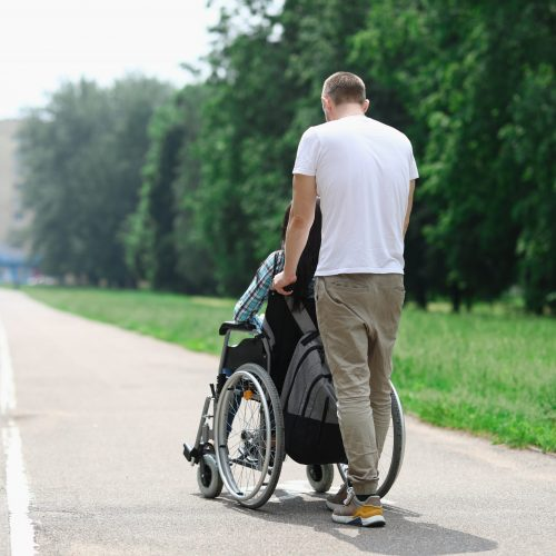 Man rolls wheelchair with girl down street. Relationship with a disabled person and walking together concept